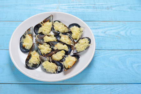 Plate with baked mussels with cheese and onions on a blue wooden background