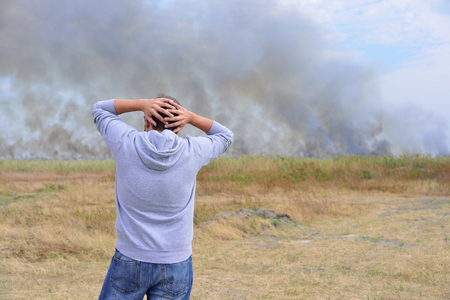man looks at a burning field Stock Photo