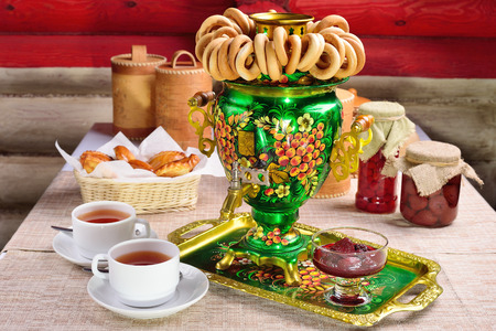 Russian character - a samovar. A bunch of bagels. Homemade jam. Patties. Russian food. Imagens