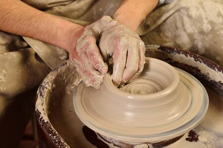 Creating a jar or vase. Master crock. Man hands making clay jug. The sculptor in the workshop makes a jug out of earthenware closeup. Potters wheel. Pottery concept.