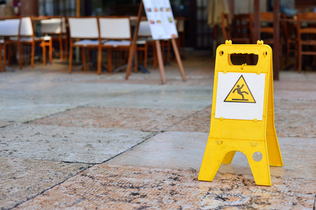 Sign showing warning of caution wet floor outdoors.