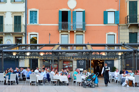 eating area: VERONA, ITALY - MAY, 2017: Summer terrace of the restaurant in the center of Verona near the arena. People are eating dinner. Rest of tourists.