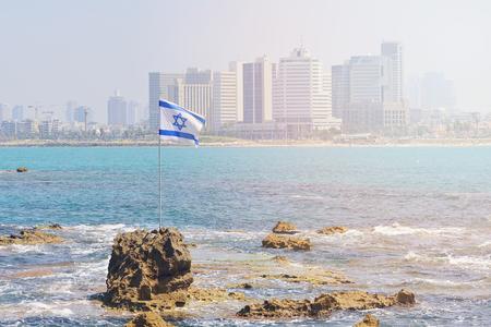 The flag of Israel against the background of modern Tel Aviv, the Mediterranean Sea.