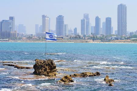 TEL AVIV, ISRAEL - APRIL, 2017: The flag of Israel against the background of modern Tel Aviv, the Mediterranean Sea.