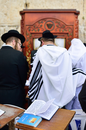gods: JERUSALEM, ISRAEL - APRIL 2017: Talmud Tora Tanach Books lying on table during prayer in Bar Mitzwa Ceremony at the Western Wall Jerusalem (Kotel) with people in the background