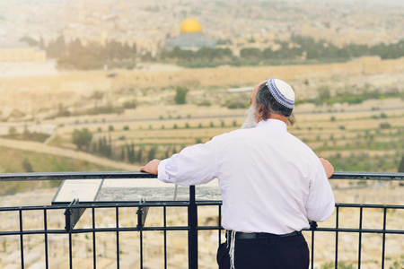 Orthodox Jew on the background of Jerusalem. The concept of religion. The touristic image of Israel.