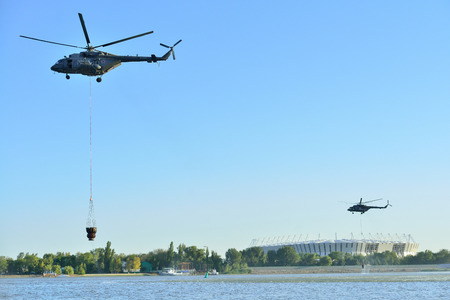 ROSTOV-ON-DON, RUSSIA - AUGUST 21, 2017: military helicopters collect water from the don river to extinguish a fire, Rostov-on-don, Russia.