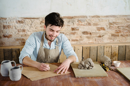 the smiling handsome young mexican potter does sketches of ceramics on the paper. concept of small business, handcrafted, hobby work.