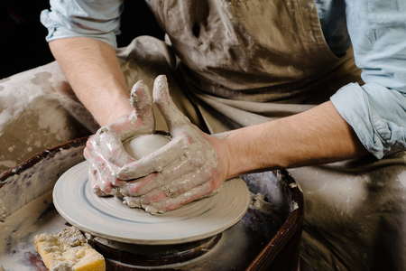 fireclay: pottery, workshop, ceramics art concept - closeup on male hands sculpt new utensil with a tools and water, mans fingers work with potter wheel and raw fireclay, front close view Stock Photo