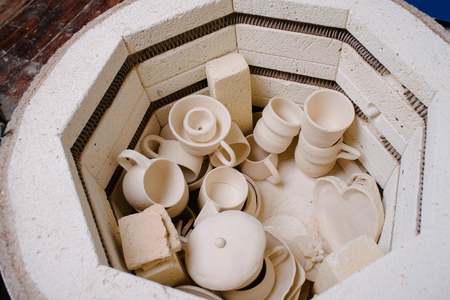 ceramicist: Roasted ceramic products without glaze in the potters hands. Top view. Art and small business, hobby and freelance working concept. Pottery making kiln ready for the firing process.