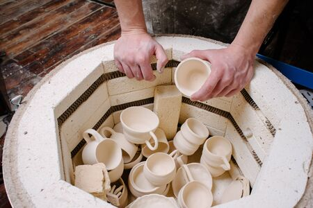 ceramicist: pottery, workshop, ceramics art concept - closeup on male hands gently puts the jug in the kiln, top view of electric oven for further roasting of unfinished clay products, cups and unbaked utensils