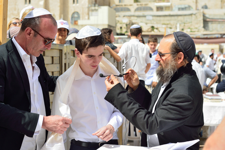 JERUSALEM, ISRAEL - APRIL 2017: Bar Mitzvah ritual at the Wesern wall in Jerusalem, Israel.Boy who has become a Bar Mitzvah is morally and ethically responsible for his decisions and actions. Editorial