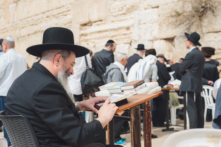 JERUSALEM, ISRAEL - APRIL 2017:  An Orthodox Jew reads the Talmud near the western wall. The Western wall or Wailing wall is the holiest place to Judaism in the old city of Jerusalem, Israel.