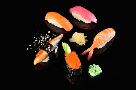 Salmon and tuna, shrimp, eel, flying fish roe sushi, dark background. Concept menu of a Japanese restaurant.