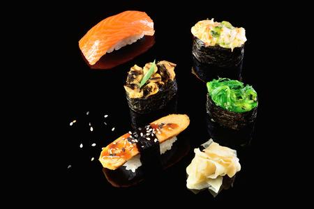 Salmon and mussels, salad shrimp, chuka, Japanese omelette sushi, dark background. Concept menu of a Japanese restaurant.