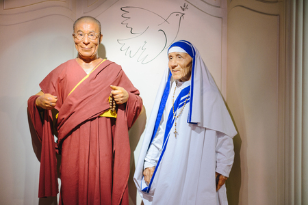 PRAGUE, CZECH REPUBLIC - MAY 2017: The wax figures Dalai Lama and Mother Teresa in the Madame Tussaud Museum in Prague, Czech Republic. Dove of peace between as symbol of love and peace.