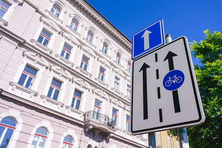 bicycle lane sign against a blue sky and buildings at the background 스톡 콘텐츠