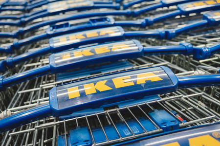 ST. PETERSBURG, RUSSIA - MARCH, 2019: line of Ikea shopping carts. Ikea is a famous Scandinavian chain selling ready-to-assemble furniture, plus housewares, in a warehouse