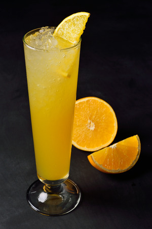 Ice cold citrus cocktail in a hight glass. Dark background with copy space for a menu.