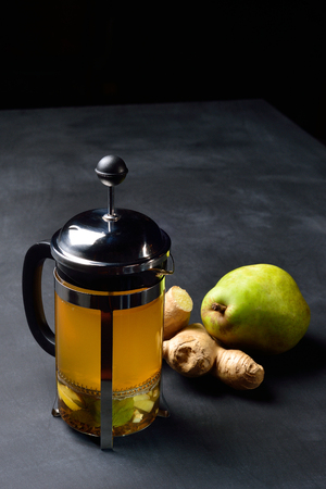 Teapot with ginger tea and pear on dark background.