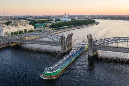 Saint Petersburg. Russia. Bolsheokhtinsky bridge lifted. Bridge of Peter the Great at sunset. The drawbridges of Petersburg. Navigation on the Neva River. Cities of Russia. Panorama of St. Petersburg. 写真素材