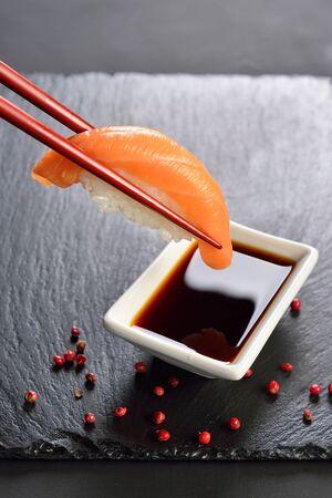 sushi sake in chopsticks dipped in soy sauce