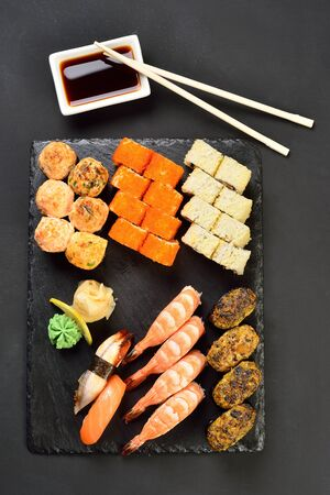 Sushi Set and sushi rolls served on stone plate