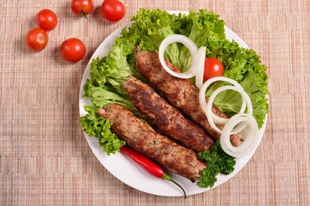 Lula kebab is a traditional Arabic dish. Meat shashlik on  with tomato. The top view 写真素材
