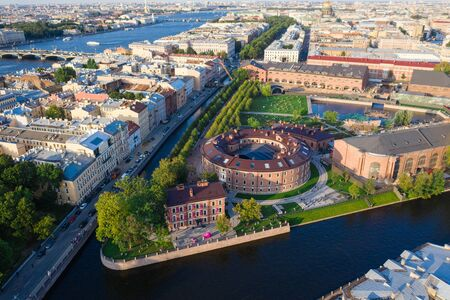 Aerial drone view of historical city part with old architecture and modern park between two artificial river channel, round building in the center, new Holland, Saint Petersburg, Russia 写真素材
