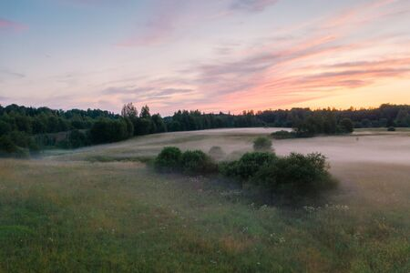 Magnificent sunset and mist spreading across the field, Leningrad region, Russia