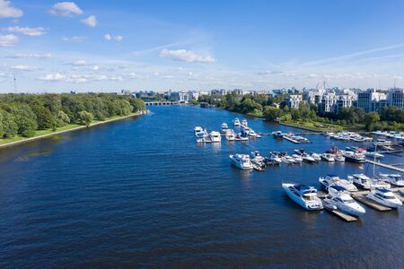 Yachts and river boats moored to the pier of Krestovsky island, the river Average Nevka, in the summer Imagens