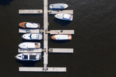 Aerial View by Drone of Yacht Club and Marina. Top view of yacht club. White boats in sea water. Marina dock yachts and small motor boats. Yacht and sailboat is moored at the quay. Parking Imagens