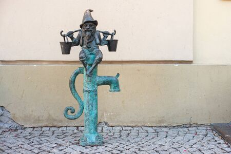 WROCLAW, POLAND - JUNE 17: Wroclaw street dwarf bronze statue with buckets sits on the water pump. Standard-Bild - 138049040