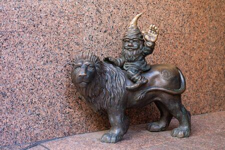 WROCLAW, POLAND - JUNE 17: Wroclaw street dwarf on the lion bronze statue.