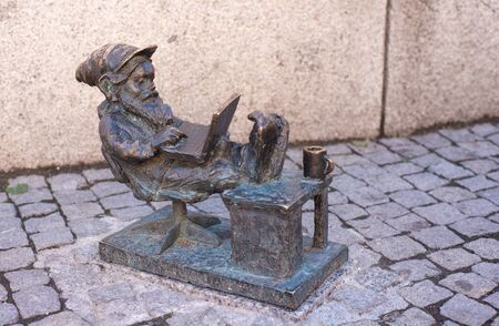 WROCLAW, POLAND - JUNE 17: Dwarf is sitting and reading a book, famous bronze miniature gnome with hat sculpture is a symbol of Wroclaw in old historical city centre Redakční