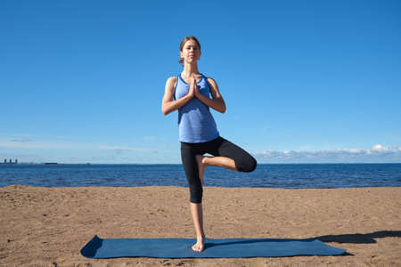 Young slim girl doing yoga on the beach on a sunny morning, stretching before doing sports