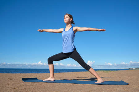 Young slim girl doing yoga on the beach on a sunny morning, positive attitude, healthy lifestyle