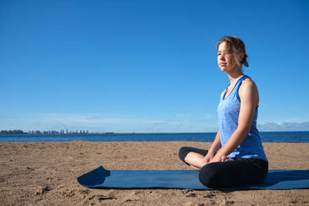 Young slim girl doing yoga, lotus position on the beach, relaxation and meditation 免版税图像