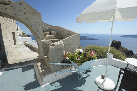 flourished: Sea view. Picturesque flowered terrace with wheelbarrow and parasol, overlooking the Aegean Sea south, in the Cyclades islands. Santorini, Greece, Europe. Stock Photo