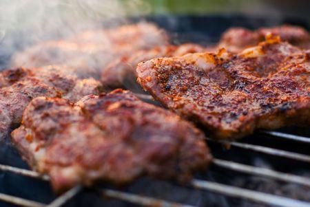 고기의: Delicious chuck steaks on the grill. Shallow depth of field.