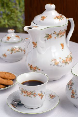 Coffee set on the table - cup of coffee on the front (focus on it) coffee pot, cookies and sugar bowl behind. photo