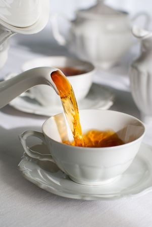 pour: Pouring tea from porcelain tea-kettle into white cup.