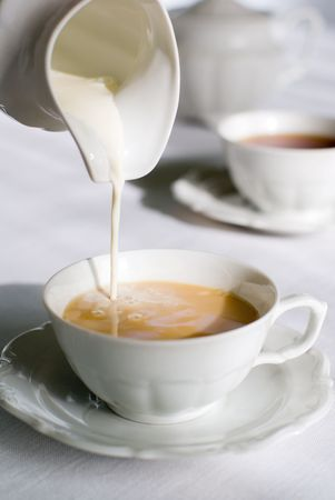 warm drink: Pouring milk from porcelain milk jug into cup filled with tea. Stock Photo