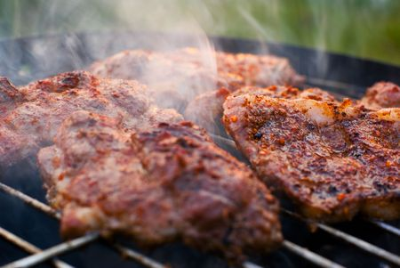 chuck: Delicious chuck steaks on the grill. Shallow depth of field.
