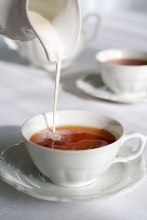 Pouring milk from porcelain milk jug into cup filled with tea - white tablecloth background. Stock Photo