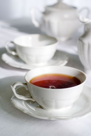 assam tea: Tea set - two teacups, one with steaming hot tea, sugarbasin behind. Focus on teacup, shallow depth of field. Stock Photo