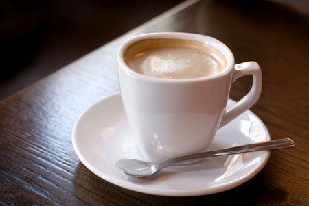 Cup of coffee (focus on the froth surface) on the cafe table. Shallow depth of field. photo