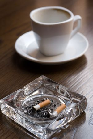 Ashtray and empty coffe cup on the cafe table. Shallow depth of field (focus on the cigarette butt). photo