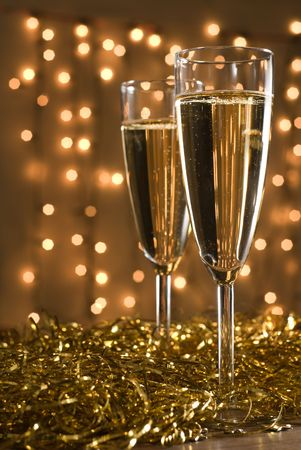 brindisi champagne: Due flauti champagne tra nastri d'oro, defocused luci sullo sfondo - shallow DOF, si concentrano sul primo vetro.  Archivio Fotografico