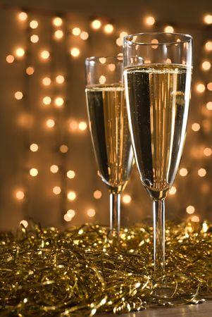 dwarsfluit: Twee champagne fluiten onder gouden linten, defocused lampjes op de achtergrond - ondiepe DOF, focus op het eerste glas.